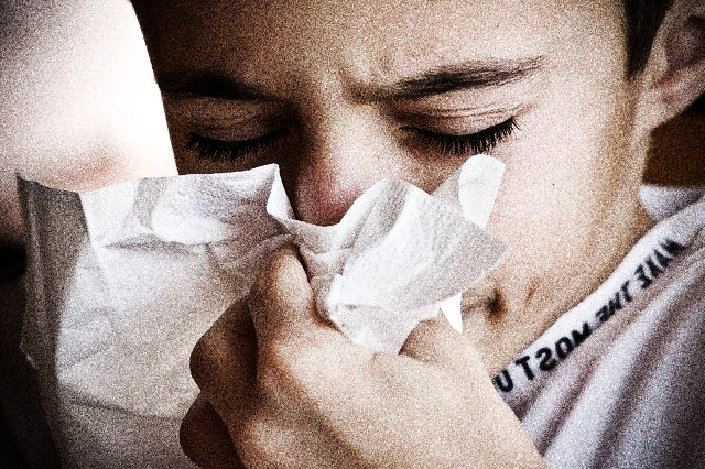 Child wiping nose from sneezing